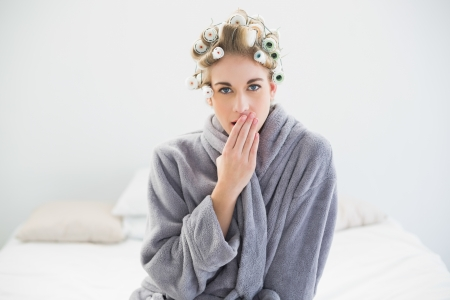 Attractive relaxed blonde woman in hair curlers yawning in a bedroom photo