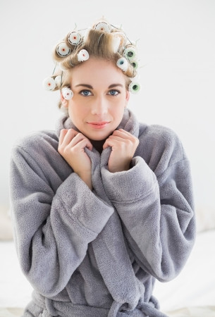 hair curlers: Lovely relaxed blonde woman in hair curlers looking at camera in a bedroom