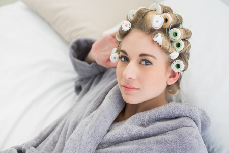 hair curlers: Beautiful relaxed blonde woman in hair curlers looking at camera in a bedroom Stock Photo
