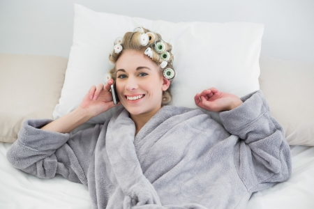 hair curlers: Cute relaxed blonde woman in hair curlers calling with her mobile phone in a bedroom