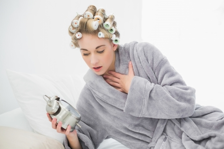 Stressed blonde woman in hair curlers looking at her alarm clock in a bedroom photo
