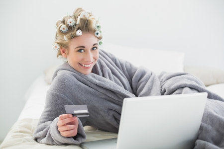 Joyful relaxed blonde woman in hair curlers buying online with her laptop in a bedroom photo