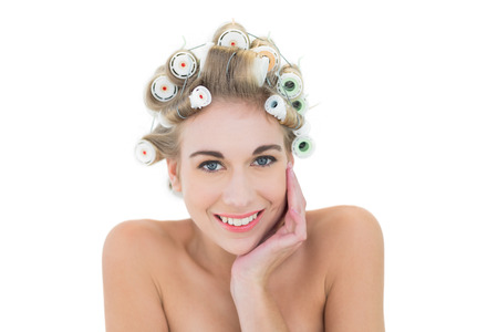 Cheerful blonde model in hair curlers holding her head on white background photo