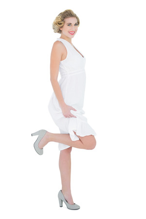 Attractive fashion blonde model posing with a leg up on white background photo