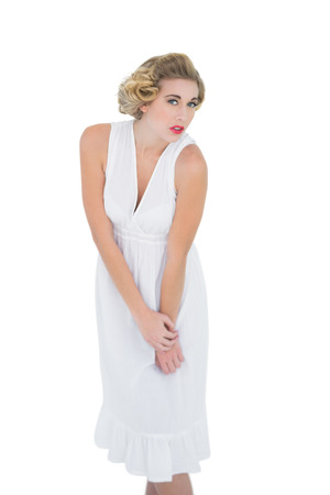 Stern fashion blonde model looking at camera on white background photo