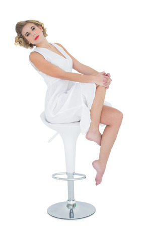 Gorgeous fashion blonde model posing sitting on bar chair on white background photo