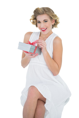 Delighted fashion blonde model opening a gift on white background photo