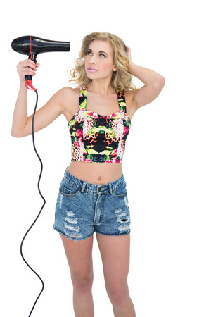 Concentrated retro blonde model using a hair dryer on white background Stock Photo - 22326843