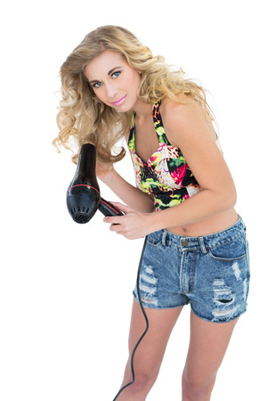 Happy retro blonde model using a hair dryer on white background photo