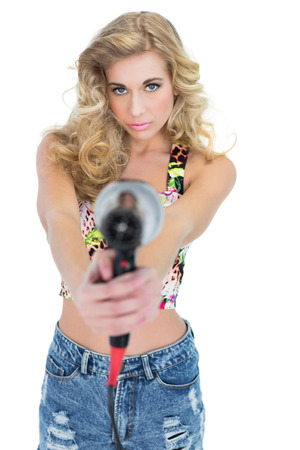 Unsmiling retro blonde woman pointing a hair dryer to the camera on white background photo