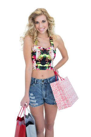 Amused retro blonde model carrying shopping bags on white background photo