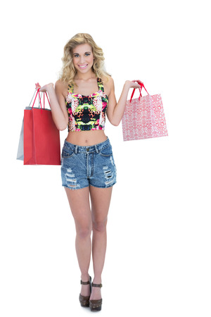 Content retro blonde model carrying shopping bags on white background photo