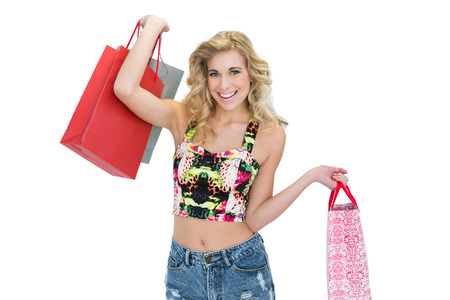 Joyful retro blonde model carrying shopping bags on white background photo