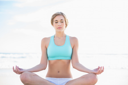Peaceful blonde woman in sportswear practicing yoga on the beach photo