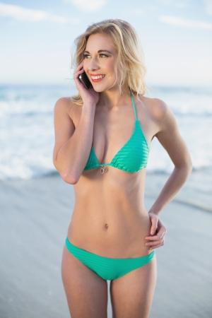 1d41783710f 緑のビキニ ビーチで彼女の携帯電話を呼び出すに金髪の女性を楽しませ の ...