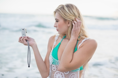 Attractive blonde woman in white beach dress taking a picture of herself on the beach photo