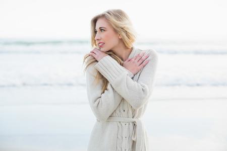 Thoughtful blonde woman in wool cardigan looking away on the beach