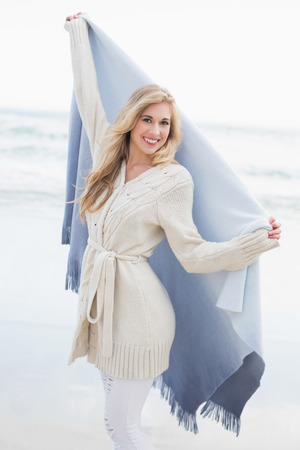 Delighted blonde woman shaking her blanket on the beach photo