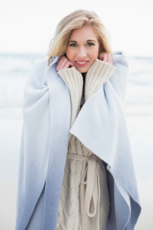 Smiling blonde woman covering herself in a blanket on the beach photo