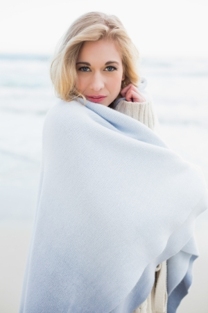 Peaceful blonde woman covering herself in a blanket on the beach photo