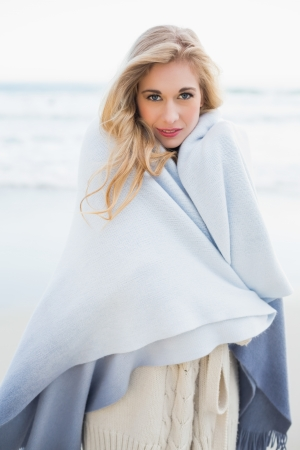 Fashion blonde woman covering herself in a blanket on the beach photo