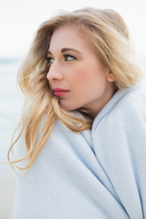 Stylish blonde woman covering herself in a blanket on the beach photo