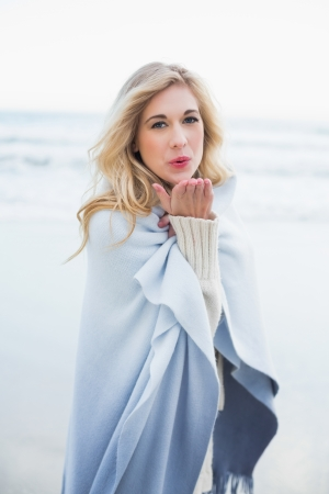 Cute blonde woman in a blanket blowing a kiss to the camera on the beach photo
