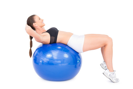 Smiling fit woman working out with exercise ball on white background  photo