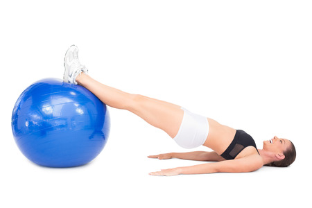 Side view of smiling fit woman lying working out with exercise ball on white background photo
