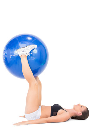 Smiling athletic woman working out with exercise ball on white background photo