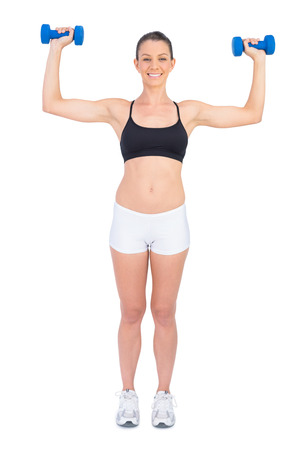Happy fit woman working out with dumbbells on white background photo