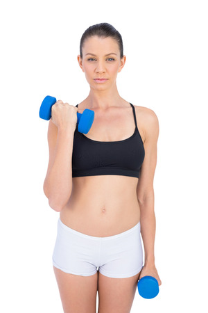 Peaceful sporty brunette working out with dumbbells on white background photo