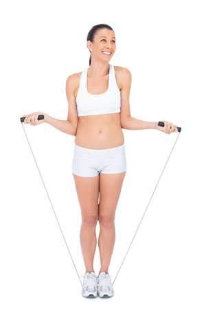 Smiling woman in sportswear exercising with skipping rope on white background photo