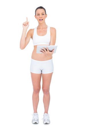 Fit woman in sportswear holding tablet and pointing up on white background Stock Photo - 22327850