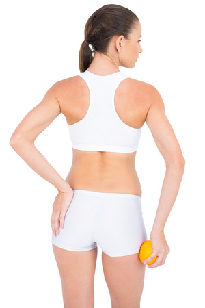 Rear view of fit woman suffering from painful pelvis on white background Stock Photo