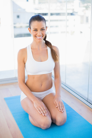 Cheerful young woman sitting on exercise mat in bright fitness studio Stock Photo - 22327891