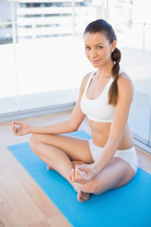 Attractive young woman meditating in lotus position in bright fitness studio photo