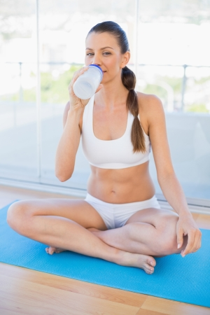 Fit young woman sitting in lotus position drinking in bright fitness studio Stock Photo - 22327894