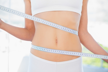 Mid section of woman measuring her waist in bright fitness studio photo