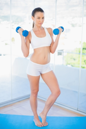 Serious fit woman lifting dumbbells in bright fitness studio photo