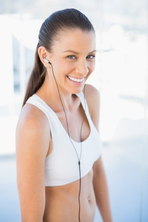 Laughing woman in sportswear listening to music in bright fitness studio