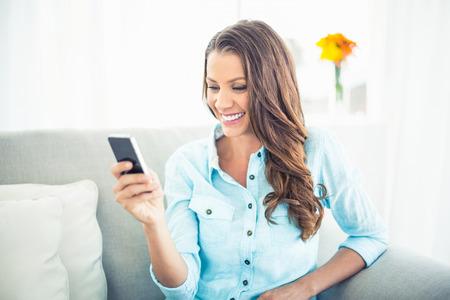 テキスト メッセージの明るいリビング ルームで居心地の良いソファの上に座って微笑んでいるモデル