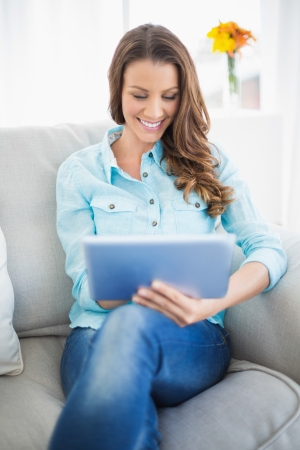 Happy woman using tablet pc sitting on cosy sofa photo