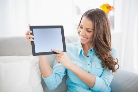 Lächelnde Frau zeigt ihre Tablet-Bildschirm sitzt auf gemütlichen Sofa