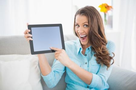 Euphoric Frau zeigt ihre Tablet-Bildschirm sitzt auf gemütlichen Sofa