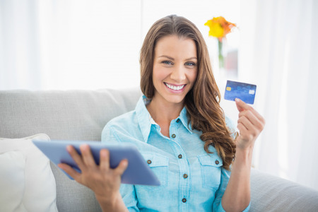 Smiling woman holding tablet and showing her credit card sitting on cosy sofa