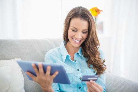 Attractive brunette holding tablet and credit card sitting on cosy sofa photo