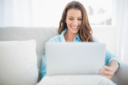 woman on couch: Happy pretty woman using laptop sitting on cosy sofa Stock Photo