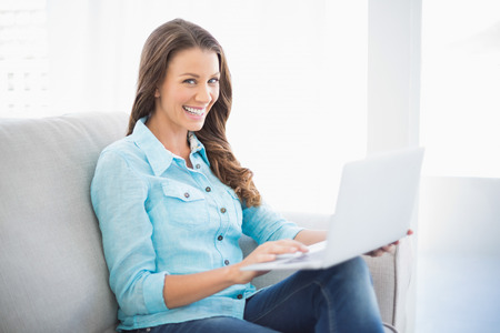 woman typing: Happy brunette sitting on sofa in bright living room using laptop