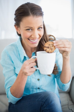 Smiling woman dunking cookie in coffee looking at camera